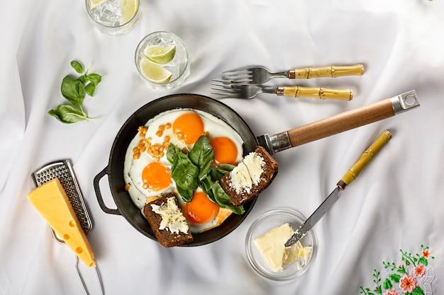 Poêle à frire avec des œufs au plat sur un espace clair. nappe blanche