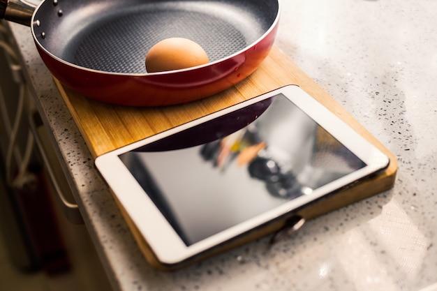 Poêle à frire avec des œufs et une tablette
