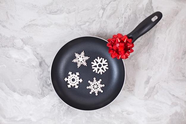 Poêle à frire ou poêle avec des flocons de neige sur une table en marbre. vue de dessus. copiez l'espace.