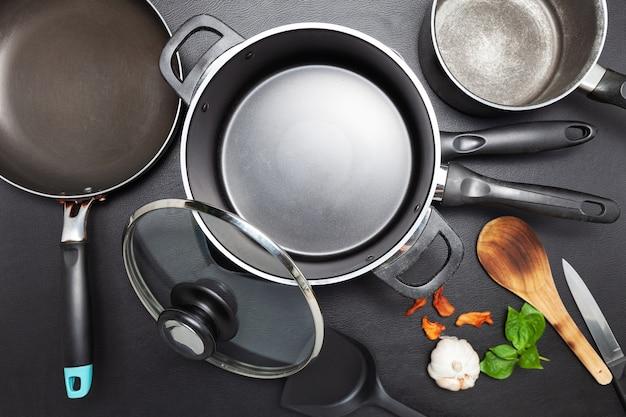 Poêle à frire et pot sur la table noire