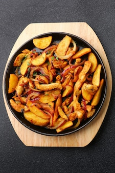 Poêle à frire avec viande de pommes de terre et oignon rôti sur fond de béton noir