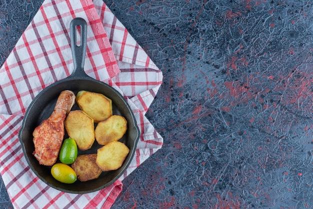 Une poêle à frire avec de la viande de poulet et des légumes