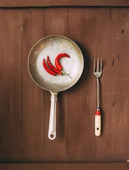 Poêle à frire vintage sur un bois sombre.