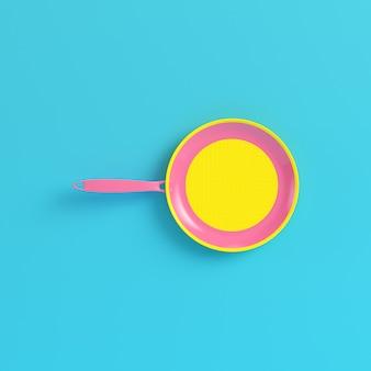 Poêle jaune sur fond bleu vif