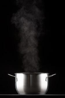 Poêle en métal sur fond noir, vient de la vapeur