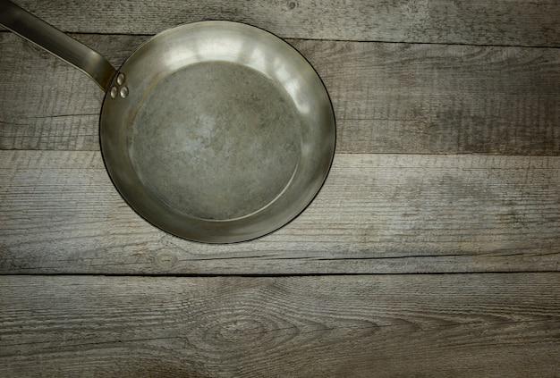 Poêle en métal vintage sur planche de bois. vue de dessus.