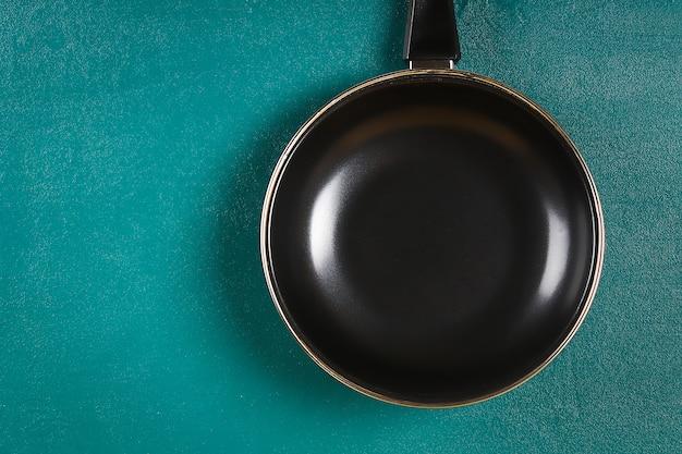 Poêle noire sur une étagère en bois sur fond bleu sarcelle