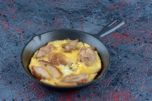 Une poêle d'omelette avec de la viande de poulet