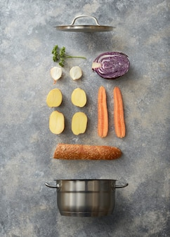 Poêle ouverte et légumes tranchés pour cuisiner avec baguette sur fond de béton gris, mise à plat
