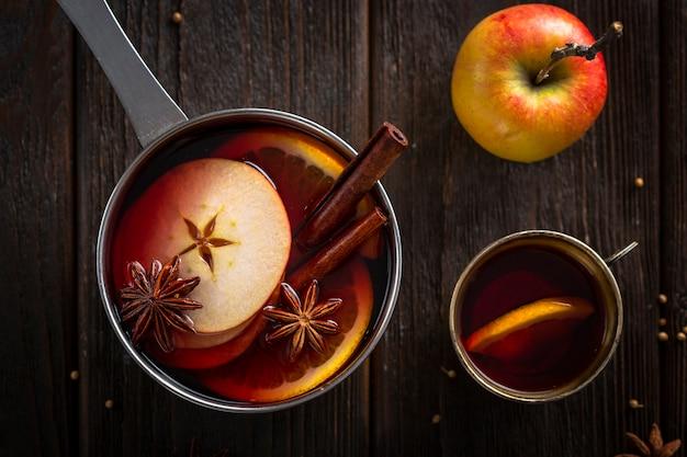 Poêle plate avec coupe de vin chaud et pomme