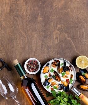 Poêle plate avec des moules en sauce blanche et du vin avec fond