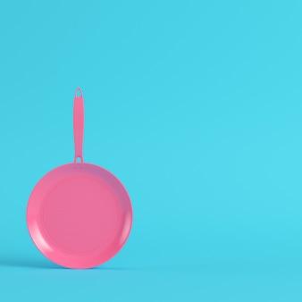 Poêle rose sur fond bleu vif