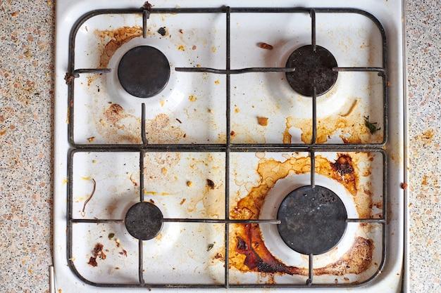 Poêle sale avec des restes de nourriture. table de cuisson à gaz sale avec taches de graisse, vieilles taches de graisse, taches de friture et éclaboussures d'huile.