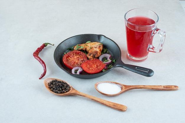 Une poêle sombre avec des tranches de tomates frites et du poulet sur blanc
