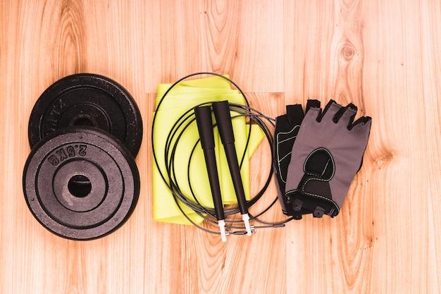 Poids et équipements de fitness sur plancher en bois