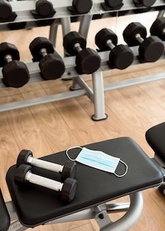 Poids et masque médical sur banc de gym