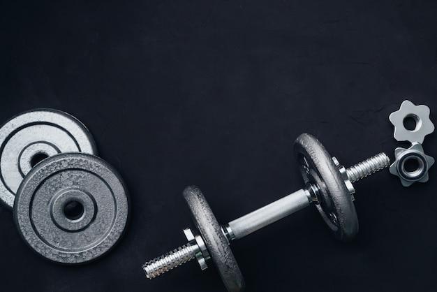 Poids métalliques et haltères à disques, pour le sport sur fond noir