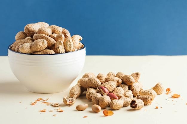 Une poignée d'arachides en coques et dans un bol. le concept d'une alimentation saine, une collation pour les végétariens, des graisses végétales. copiez l'espace. foodphoto.