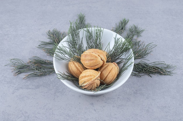 Poignée de biscuits fourrés au caramel ornés de feuilles de pin sur table en marbre.