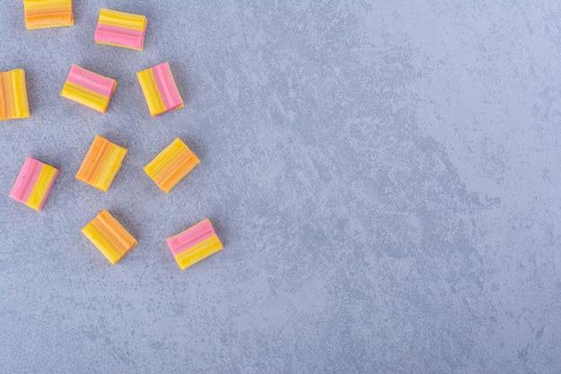Une poignée de chewing-gums oranges éparpillés sur une surface en marbre