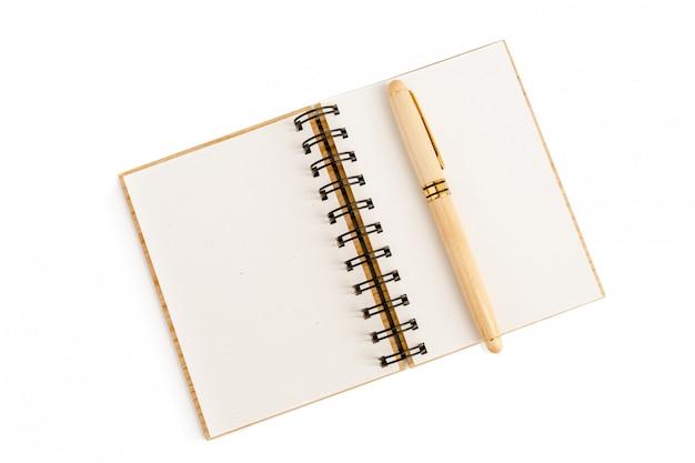 La poignée dans une caisse en bois avec un capuchon repose sur une feuille vide d'un cahier ouvert