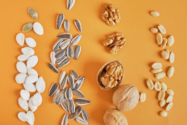 Une poignée de différentes noix et graines sur fond marron, cacahuètes, graines de tournesol, citrouille et noix