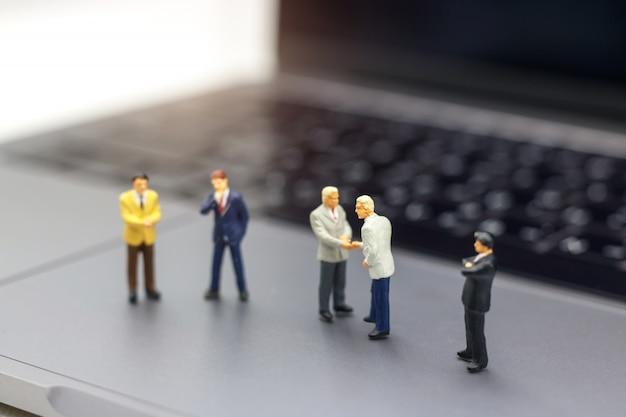 Poignée d'homme d'affaires au succès de l'entreprise en ligne sur un ordinateur portable.