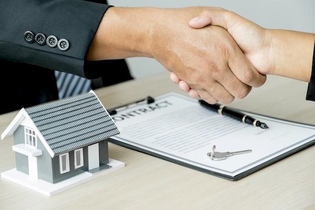Poignée de main l'agent immobilier explique le contrat commercial à l'acheteur féminin