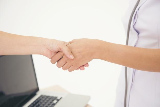 Poignée de main agrandie entre le costume blanc de l'infirmière et le patient