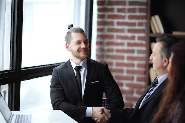 Poignée de main amicale des partenaires commerciaux assis à un bureau