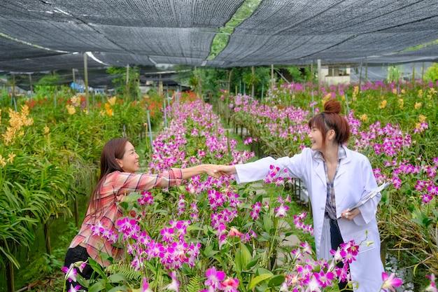 Poignée de main des chercheurs et des propriétaires de jardin d'orchidées