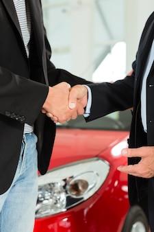 Poignée de main de deux hommes en costume avec une voiture rouge