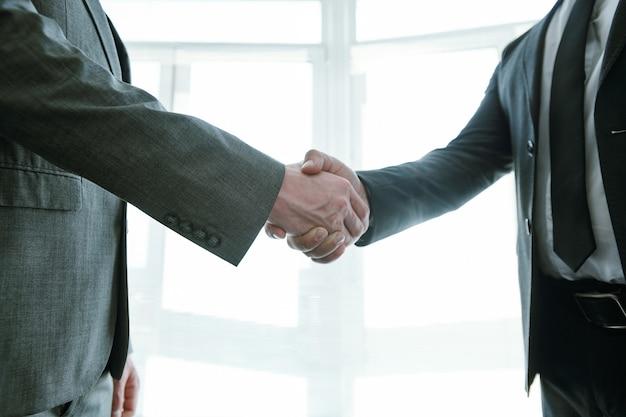 Poignée de main de deux partenaires commerciaux prospères en tenue de soirée se félicitant pour un nouvel accord ou un nouveau contrat lors d'une réunion
