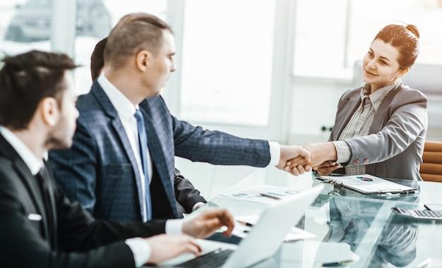 Poignée de main d'un directeur et d'un client au bureau dans le bureau. la photo a un espace vide pour votre texte