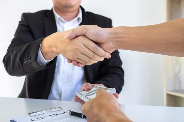 Poignée de main d'homme d'affaires avec de l'argent de billets en dollars dans les mains de l'argent de leur partenaire