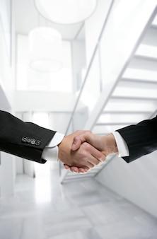 Poignée de main d'homme d'affaires sur le bureau blanc moderne