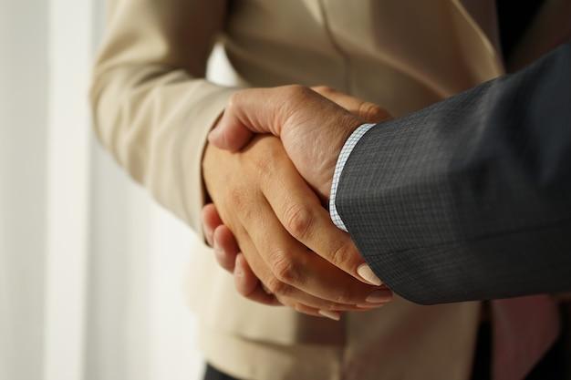 Poignée de main de l'homme et de la femme en costume d'affaires se bouchent