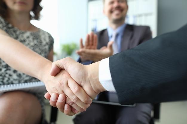 Poignée de main de l'homme et de la femme gros plan et acclamant l'homme d'affaires