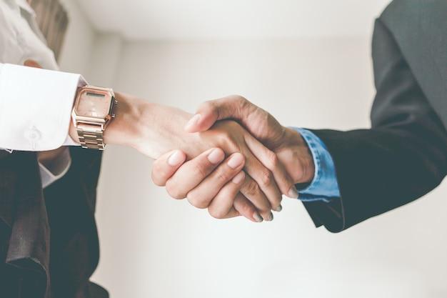 Poignée de main des hommes et des femmes d'affaires.