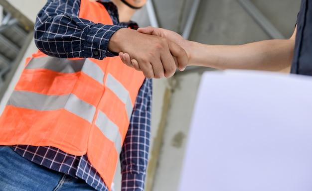 Poignée de main d'ingénieur et d'architecte asiatique sur le chantier de construction. travail d'équipe et projet de construction de lotissement réussi
