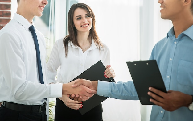 Poignée de main de jeunes partenaires commerciaux au bureau