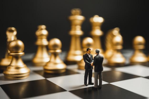 Poignée de main miniature homme d'affaires sur l'échiquier avec des échecs en or.
