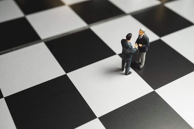 Poignée de main miniature homme d'affaires sur fond d'échiquier. concept de partenariat.