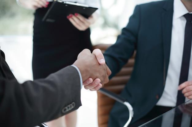 Poignée de main des partenaires commerciaux au bureau
