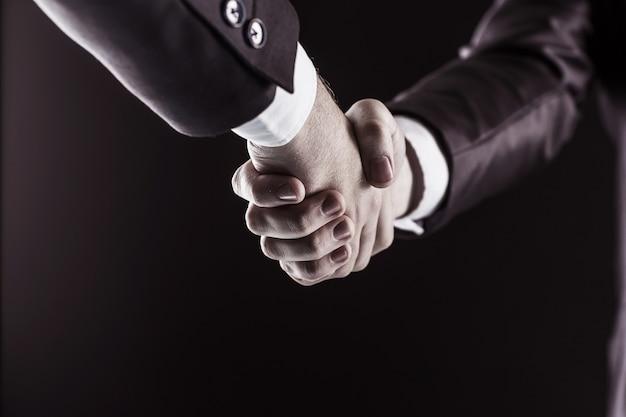 Poignée de main des partenaires commerciaux sur fond noir.