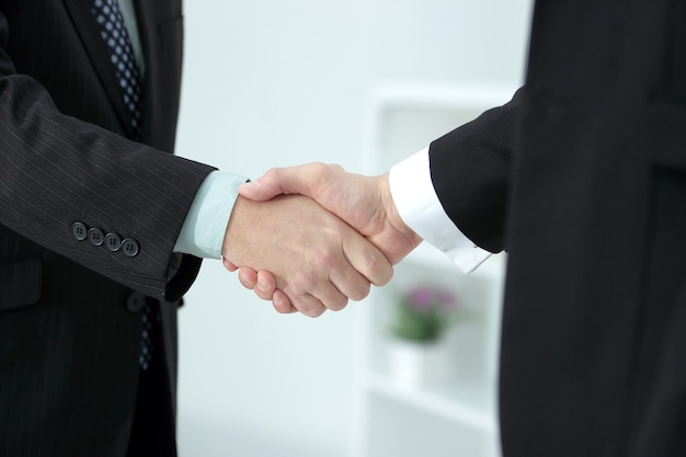 Poignée de main des partenaires commerciaux sur office flou