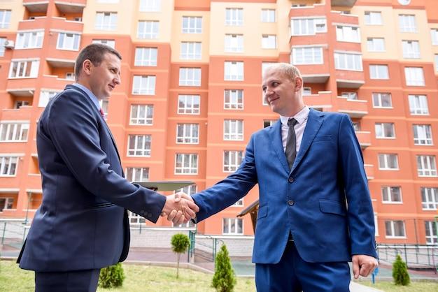 Poignée de main de partenaires commerciaux près d'un immeuble de bureaux à l'extérieur