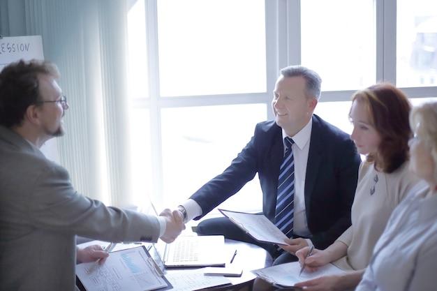 Poignée de main de partenaires commerciaux seniors