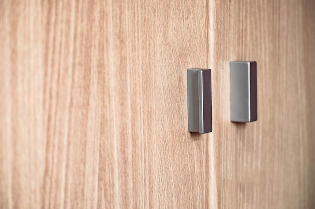 Poignée en métal sur une armoire en bois.