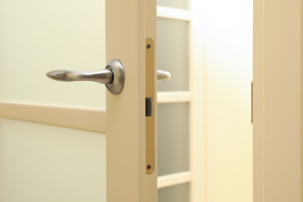 Poignée métallique de porte blanche dans la chambre